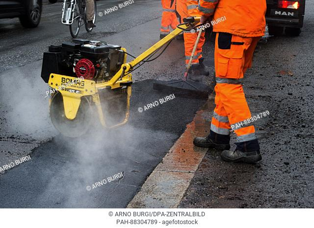 Civil engineering workers filling in potholes on a street in Dresden, Germany on 21 February 2017. Maintenance work to streets damaged by the formation of deep...