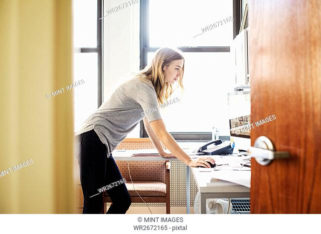 A young woman in an office standing over a desk and working at a computer