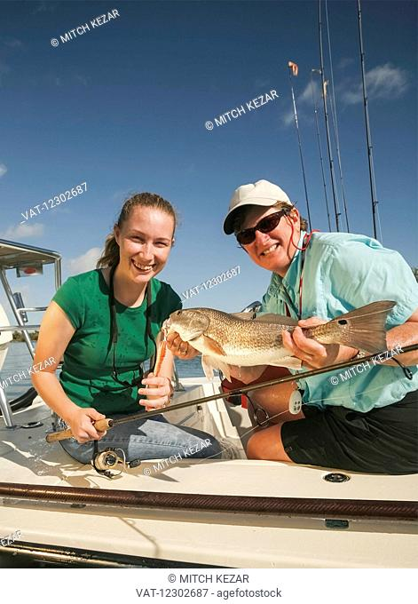 Woman Catches Redfish While Saltwater Fishing
