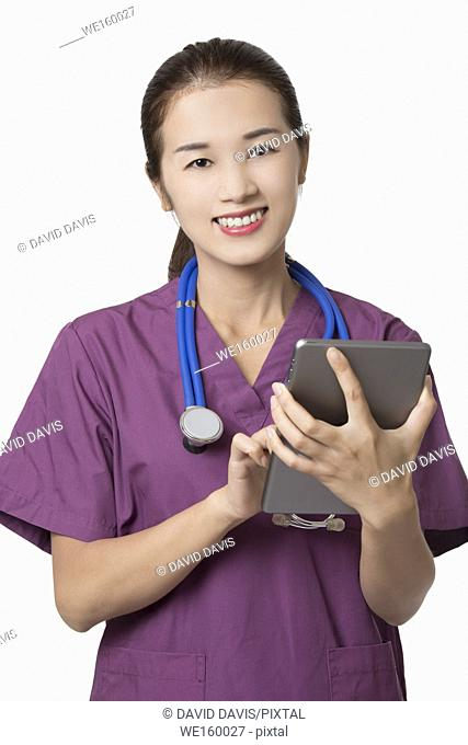 Beautiful Asian American doctor or nurse using a tablet computer with stethoscope isolated on white background