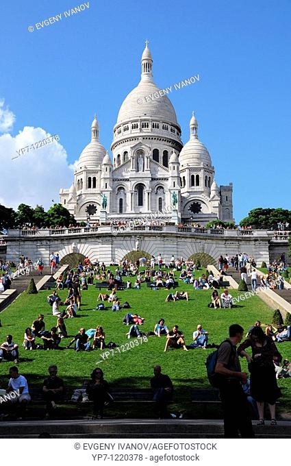 Montmartre, Paris  Basilica Sacre Coeur with tourists on green lawn