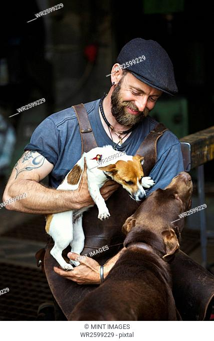 A man in a leather apron playing with two dogs in a workshop