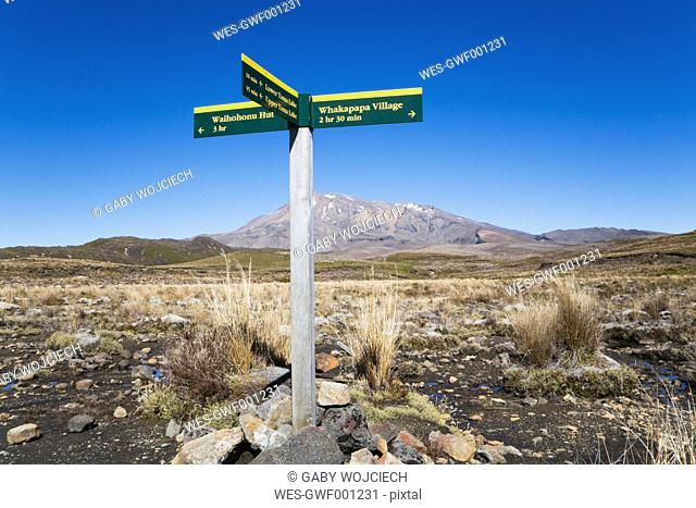 New Zealand, North Island, Hiking trail sign in tongariro national park and mount ruapehu in background