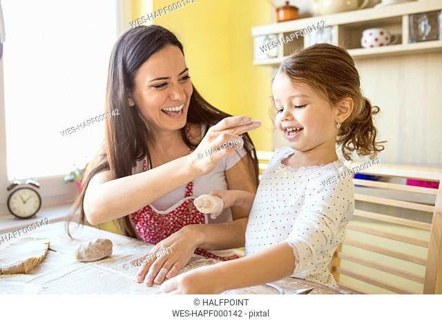 Mother and her little daughter having fun together while they are baking