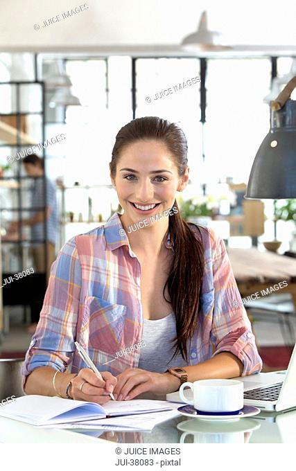 Portrait of smiling woman with coffee writing in notebook at kitchen table