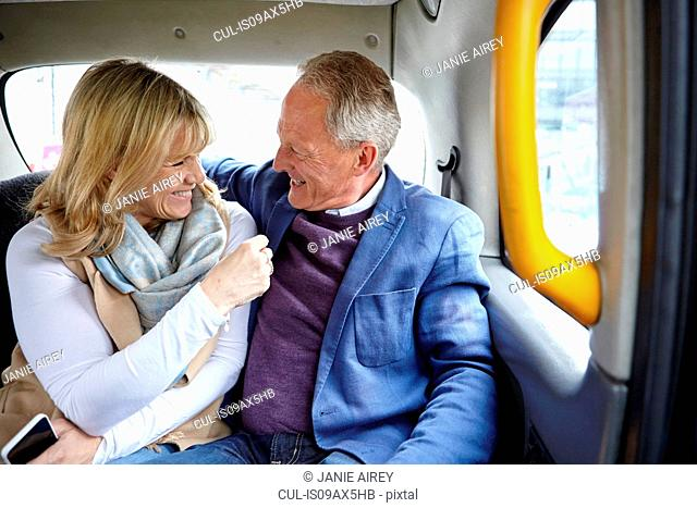 Mature dating couple en route in black cab backseat