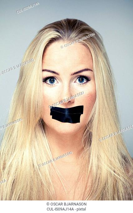 Close up studio portrait of mid adult woman with adhesive tape over her mouth