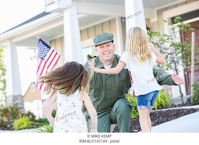 Returning Caucasian soldier hugging daughters