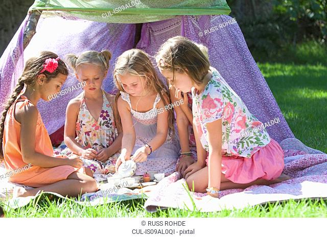 Five girls playing with toy tea set in garden