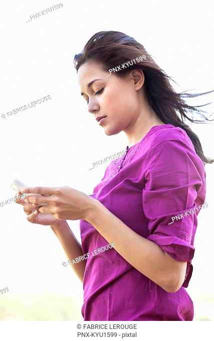 Young woman reading text message on mobile phone