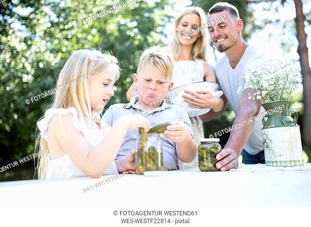 Family with preserved gherkins outdoors