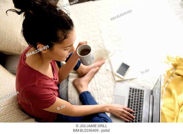 Hispanic woman sitting on bed drinking tea and using laptop