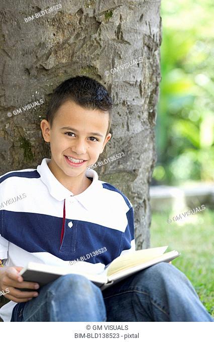 Hispanic boy reading book