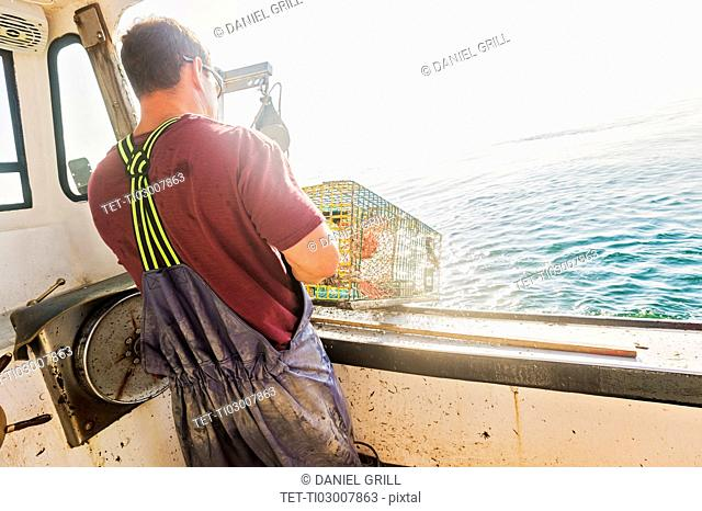 Fisherman throwing lobster trap