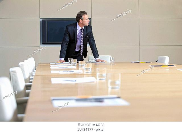 Businessman in suit leaning on table in empty conference room