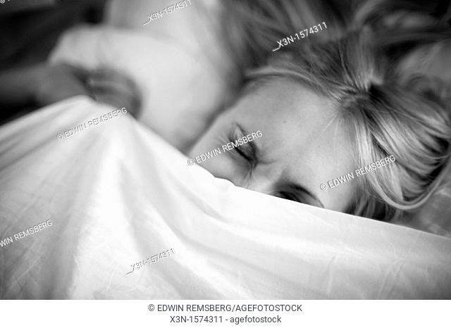 Woman in bed under covers cringing