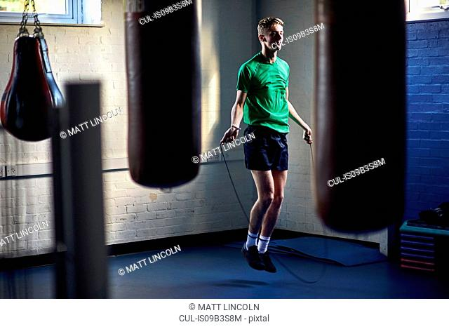 Young male boxer skipping in gym
