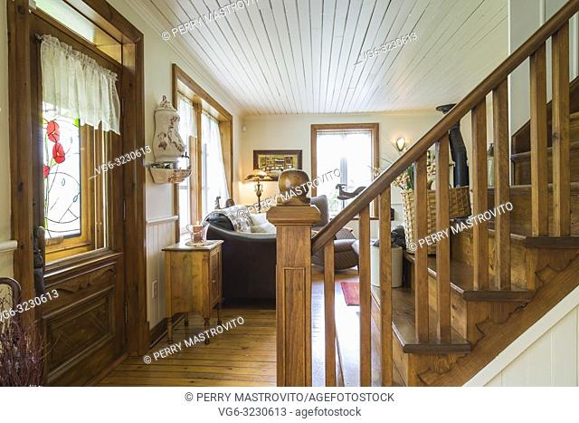 Brown stained pinewood stairs between the dining room and living room inside an old 1892 Canadiana cottage style home
