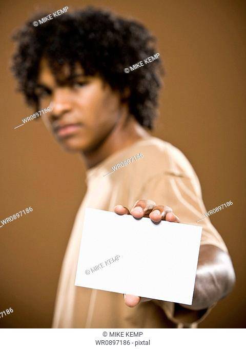 young man in a brown shirt holding a note card