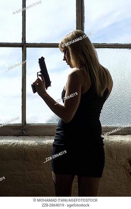 Sexy blond woman wearing a short dress holding a gun standing by the window