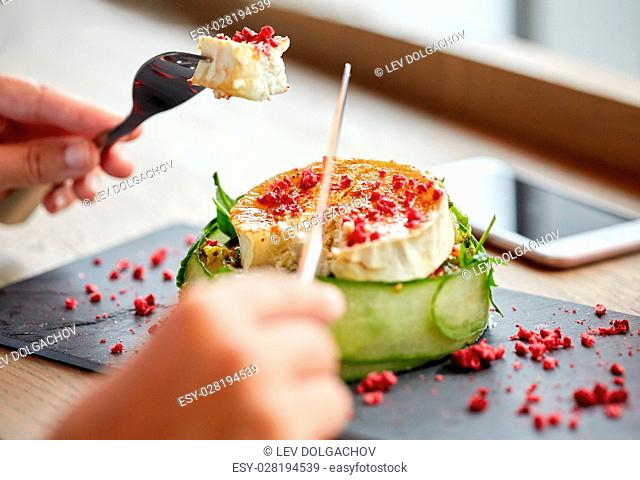 food, culinary, haute cuisine and people concept - woman eating goat cheese salad with fork and knife at restaurant or cafe