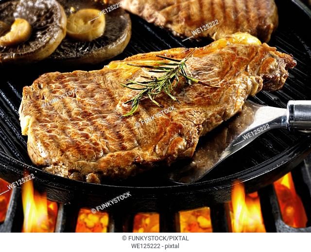 Sirloin beef steaks & mushrooms being pan fried on a bbq