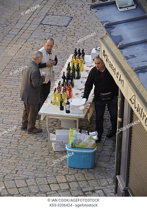 two men at a wine stall in a market, Sarlat-la-Caneda, Dordogne Department, Nouvelle-Aquitaine, France