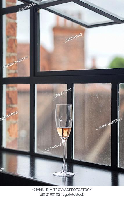 Champagne glass by window sill