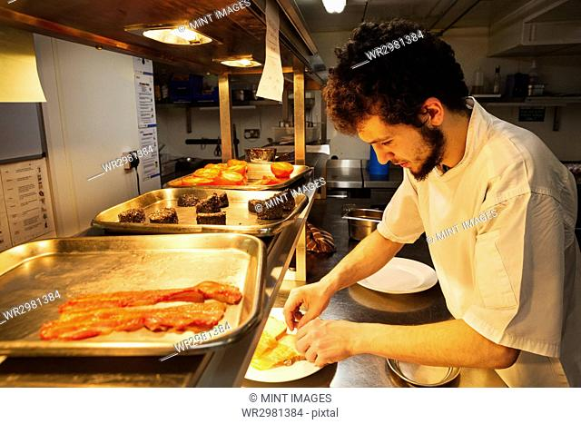 Chef standing in a restaurant kitchen at a counter plating food, trays with bacon, Black Pudding and grilled tomatoes