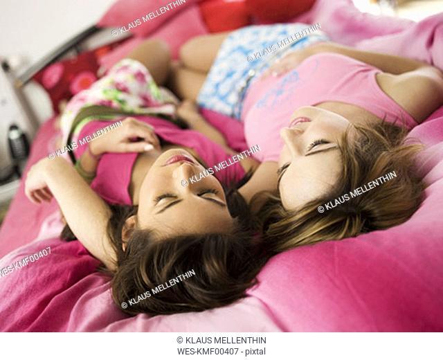 Two teenage girls lying on bed