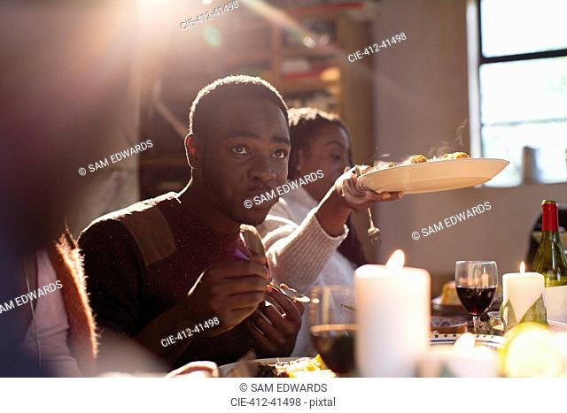 Young man enjoying Christmas dinner with family