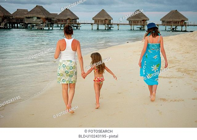 A young girl (6-8) walking with two young women on a beach