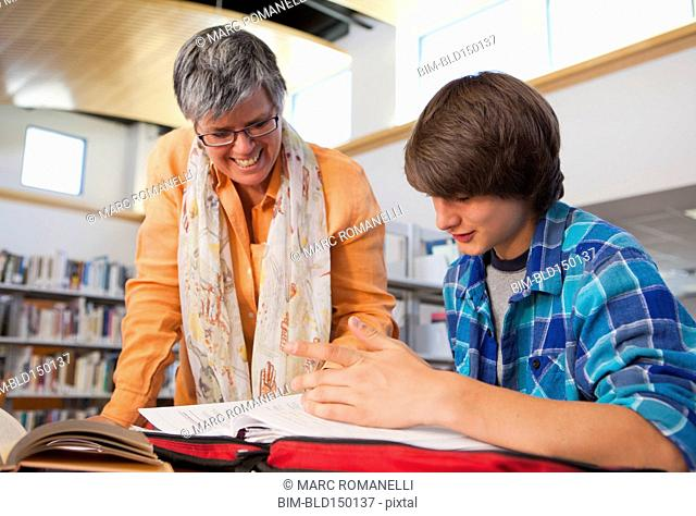 Librarian helping boy with homework in library