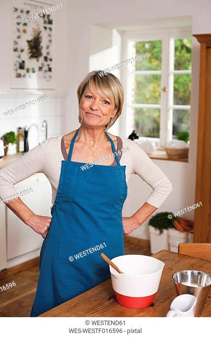 Germany, Kratzeburg, Senior woman preparing food, portrait