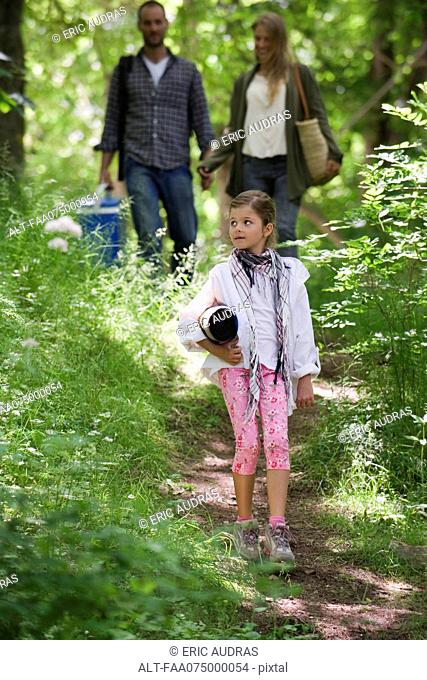 Girl walking in woods, parents in background