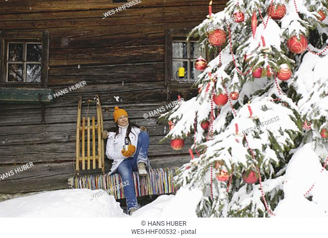 Woman sitting in front of mountain shelter, looking at christmas tree