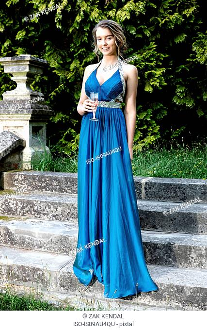 Teenage girl wearing blue prom dress standing on stairs holding champagne flute looking at camera smiling