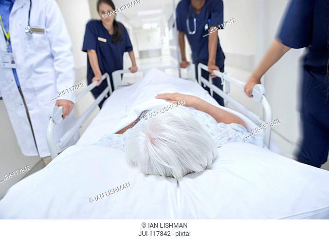 Detail Of Medical Team Wheeling Patient Along Hospital Corridor