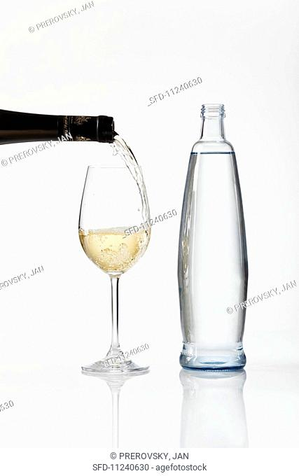 White wine being poured into a glass, next to a bottle of water