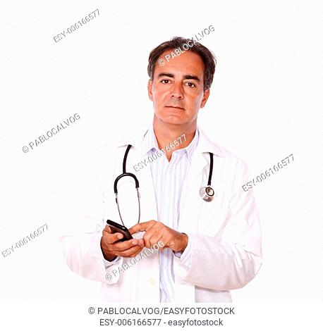 A portrait of an adult charismatic doctor on white uniform sending a message using his mobile while looking at you on isolated background