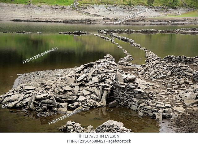 Upland reservoir with low water level and remains of submerged village exposed after dry summer, Mardale Green, Haweswater Reservoir, Mardale Valley