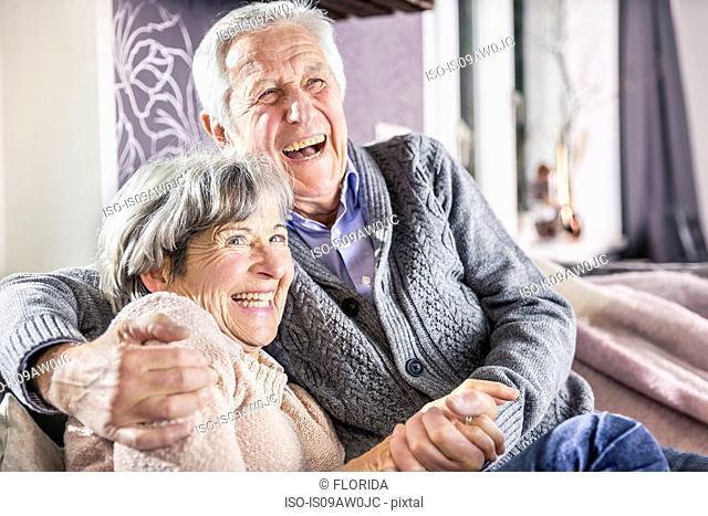 Senior couple sitting on sofa holding hands