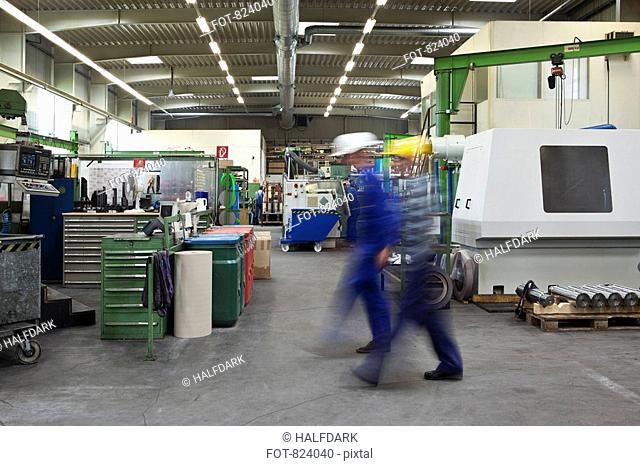 Two manual workers walking through a factory, blurred motion, long exposure