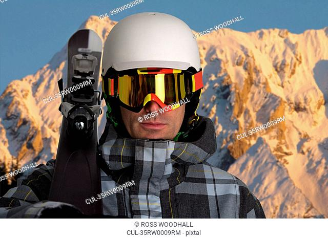 Man carrying skis in snowy mountains