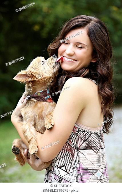 Teenage girl carrying puppy in rural field