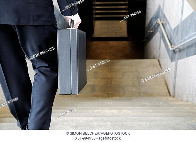 Businessman Carrying a Briefcase Going Down Stairs to a Subway Station, Rear View