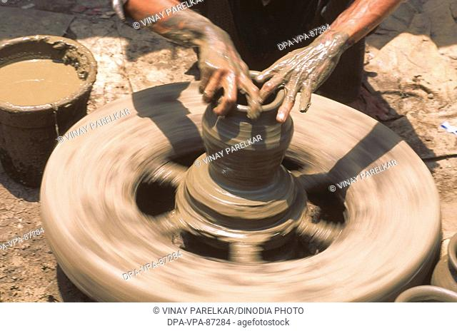 Pottery , potter hand giving shape to clay pot on wheel , Rajasthan , India