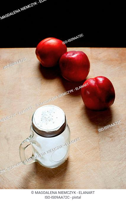 Peaches and jar of sugar, black background