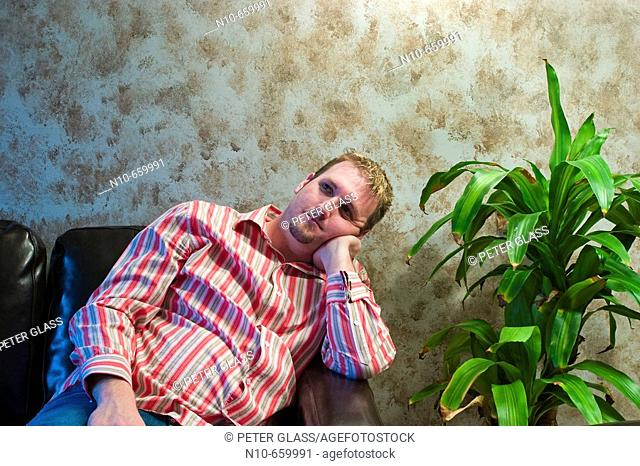 Young man sitting next to a plant