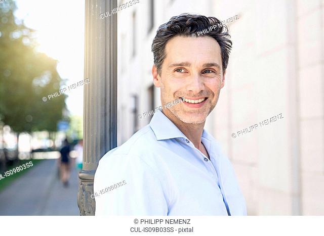 Mature man leaning against street lamppost looking sideways